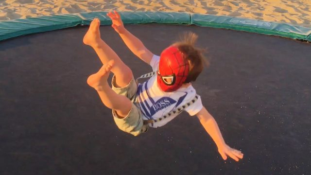 Little Boy Superhero Adam Jumping on the Trampoline with Spider-Man Mask