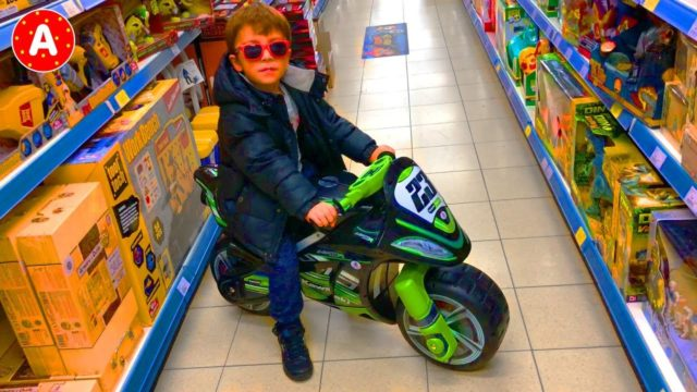 Little Boy Adam Playing with Toys in Toy Store for Kids